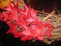 Insert leaves into grapevine wreath form. Glue with glue gun if preferred to keep leaves in place.